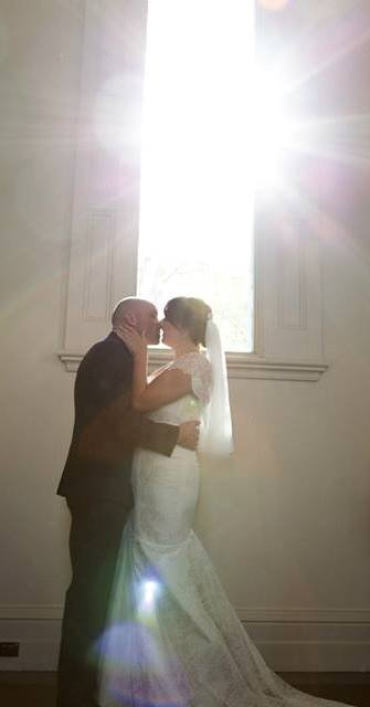 sun shining on kissing wedding couple