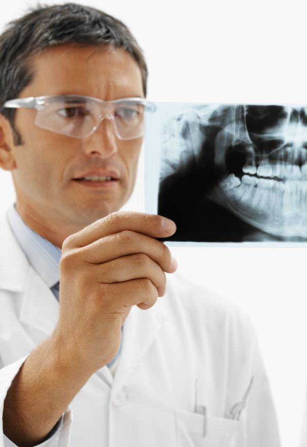 Dentist examining an x-ray to provide good oral hygiene in Middletown, NY