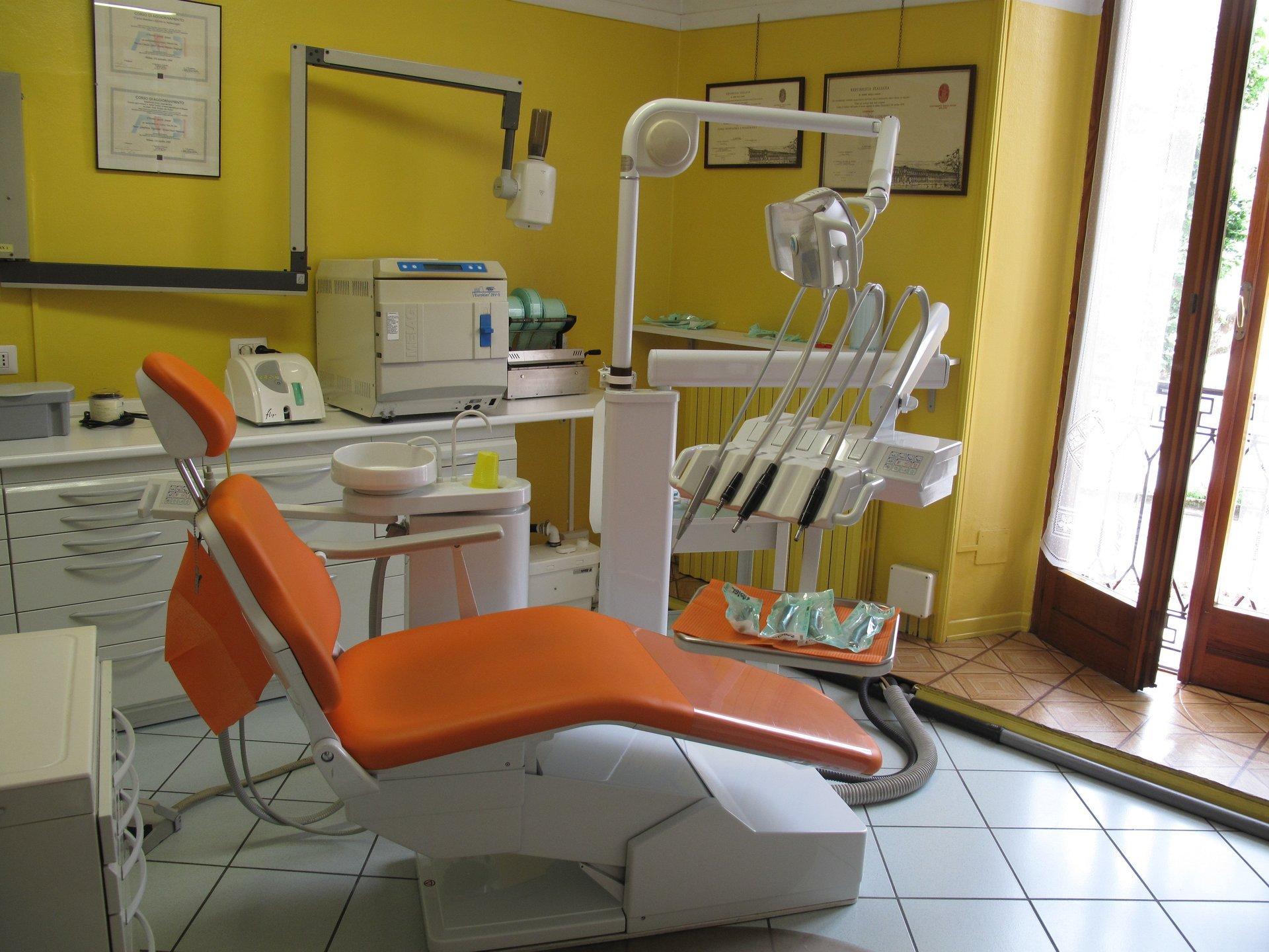 sala del dentista con poltrona arancio e pareti gialle