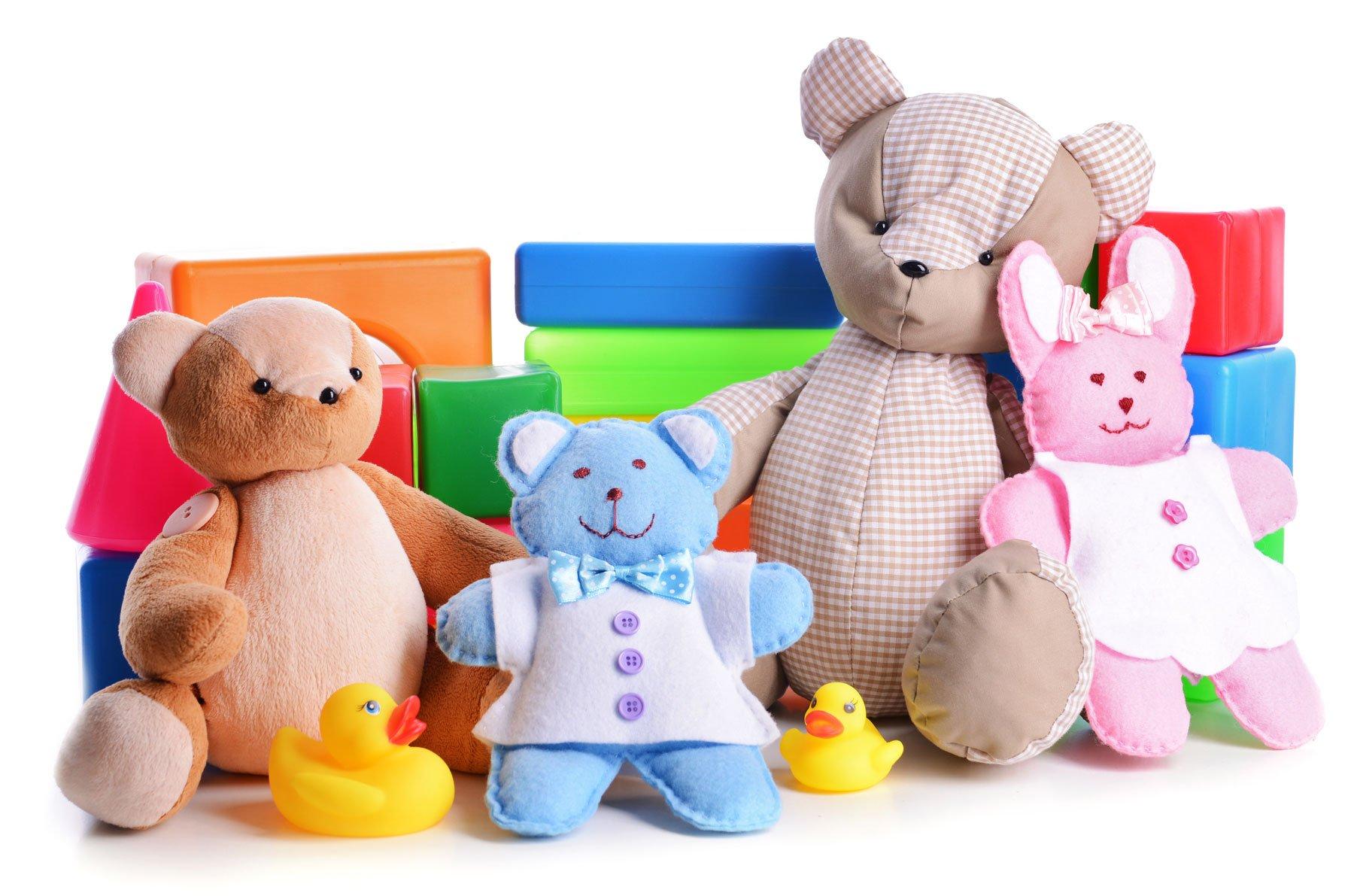 Peluche di orsi in colori marrone, beige, rosa e blu. Due paperelle di gomma, forme geometriche in plastica
