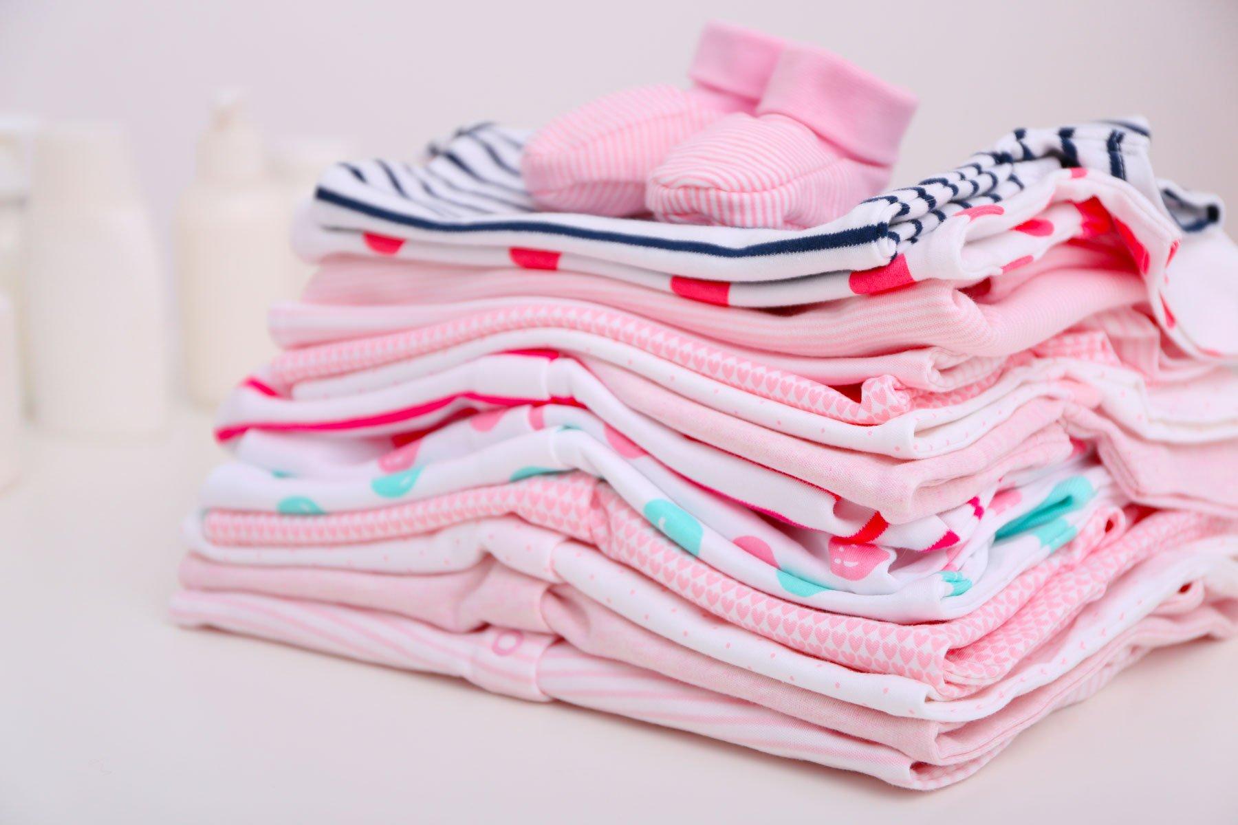 Vestiti in color rosa per bambini, piegati e messi una sopra l'altro  e scarpine spora vestiti
