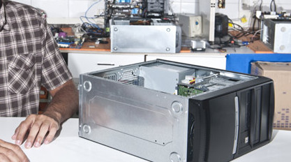 Technician next to an open desktop compter