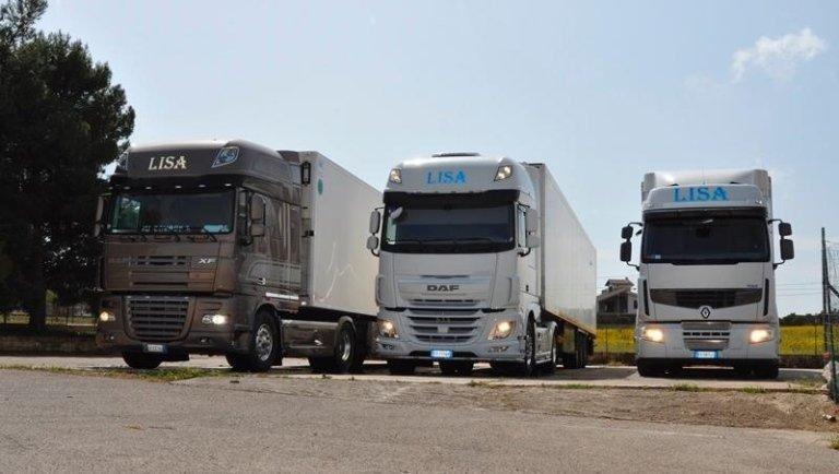 Vista laterale di tre camion,i tre con le luci accese
