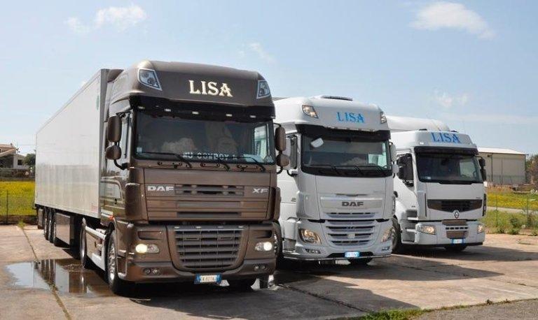 Tre camion del lato opposto, un camion marrone e due bianchi