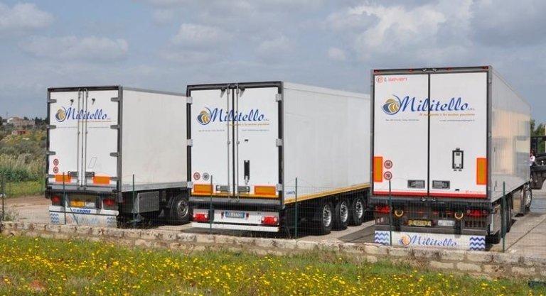 Vista posteriore di tre camion con il nome dell'impresa scritto sopra