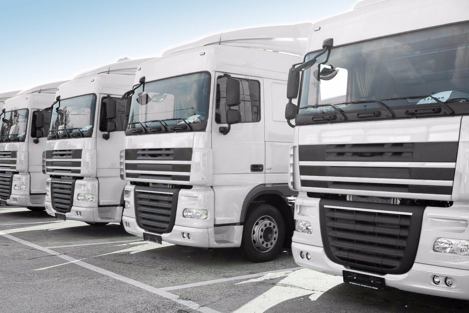 Cinque camion bianco uno accanto all'altro