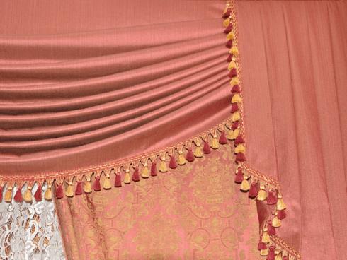 una tenda rosa pieghettata con bordi con frangette rosse  e gialle