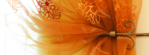 una tenda di seta arancione con disegni di fiori gialli e un gancio in ottone che la tiene alzata