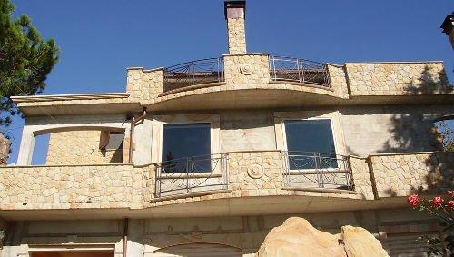 una villa in pietra di color beige con balcone e terrazza