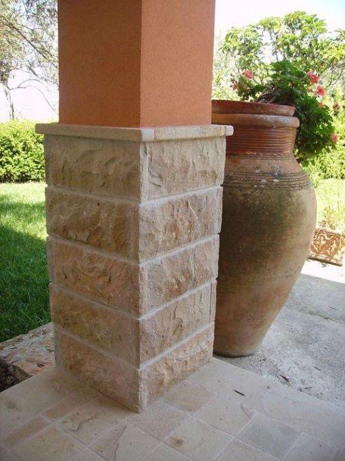 una colonna in pietra e di colore arancione accanto a un vaso di fiori