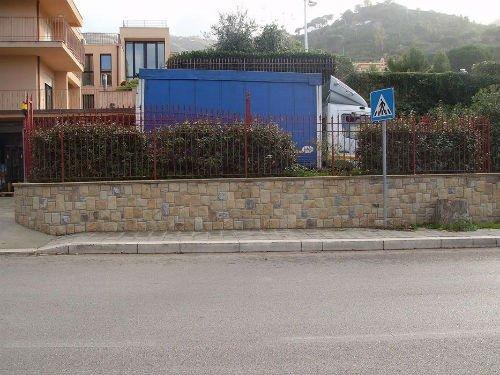 un camion davanti un edificio e un muretto in pietra