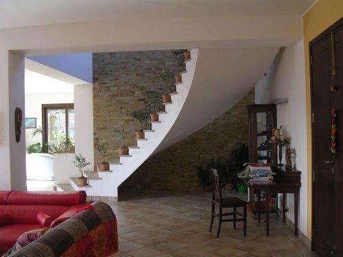 delle scale interne e accanto a un muro in pietra