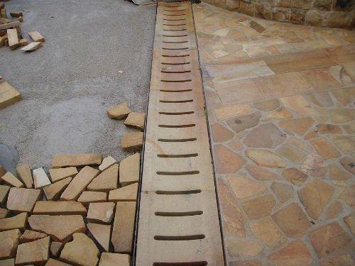 una pavimentazione in pietra e un'altra a mosaico in fase di ultimazione