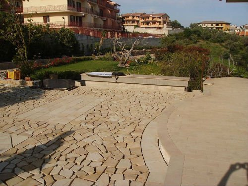 una pavimentazione a mosaico e vista di un giardino e dei condominii