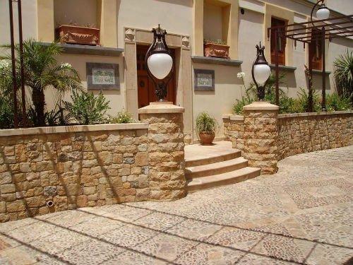 muretto in pietra,dei gradini e due lampioni vicino a una casa