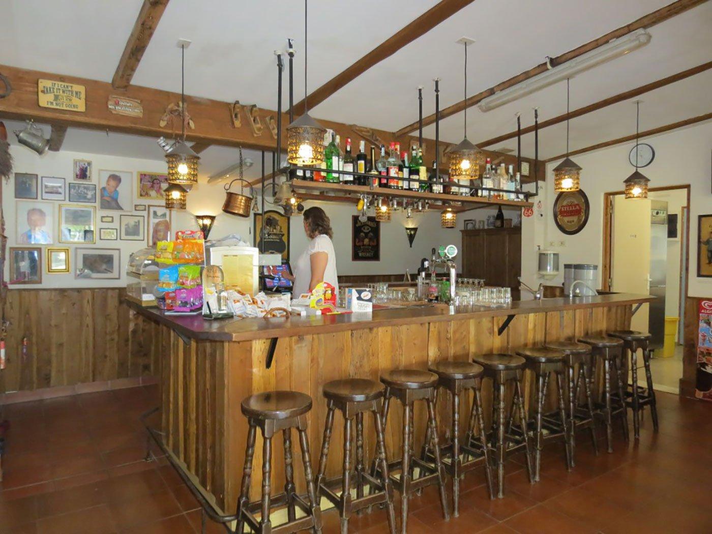 vista di un bancone in legno di un bar e una donna dietro