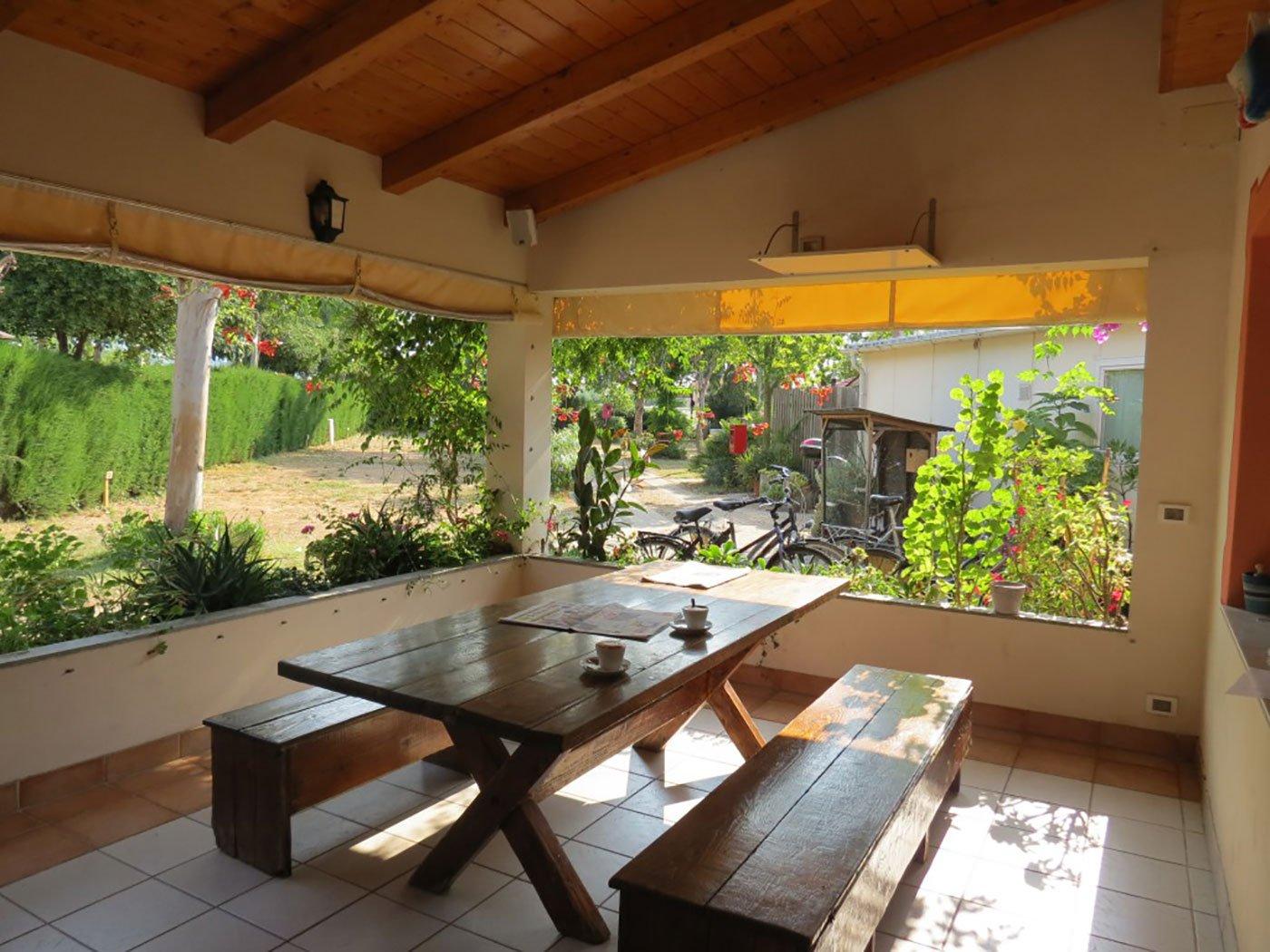 un tavolo e delle panche di legno e vista del giardino all'esterno