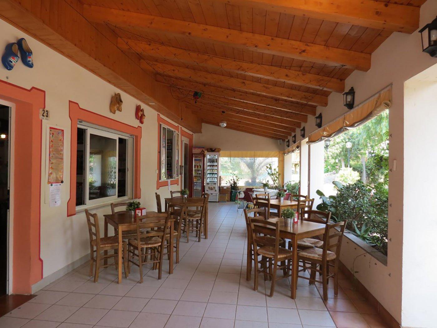 dei tavoli e delle sedie all'esterno sotto un tetto in legno