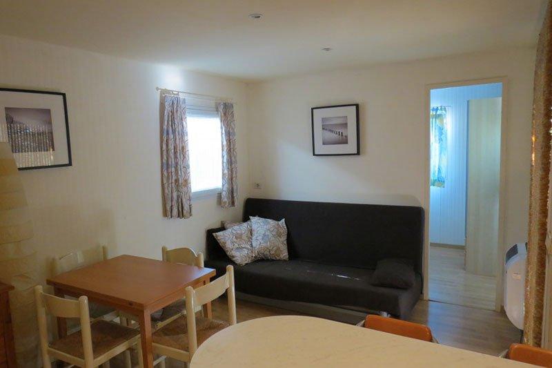 una sala con un divano di color grigio e davanti due tavoli