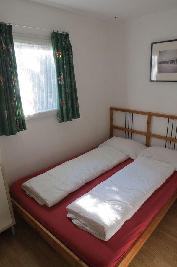 un letto con due piumini e sulla destra una finestra