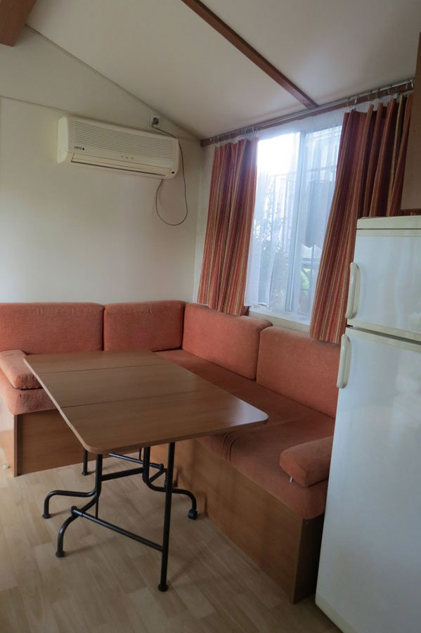un divano angolare di color rosa e sulla destra un frigorifero