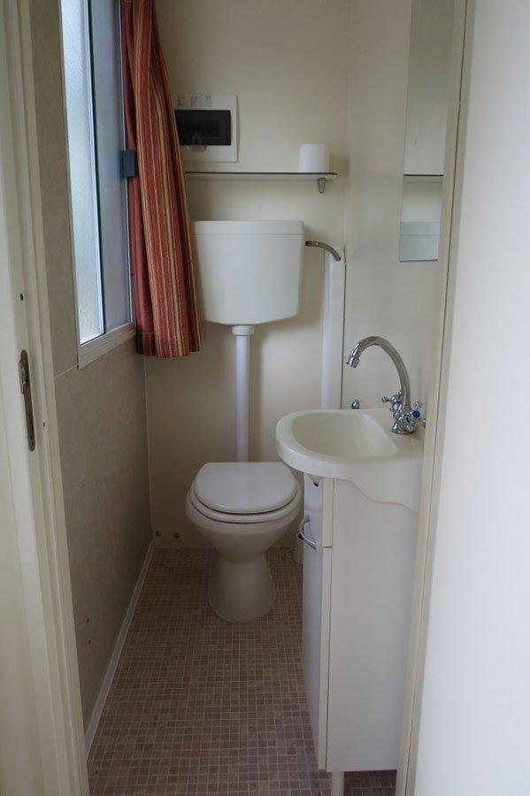 un bagno con un WC e un lavandino sulla destra