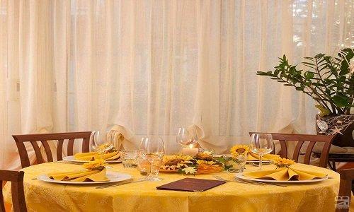 dei tavoli e delle sedie sotto a un gazebo con una tenda