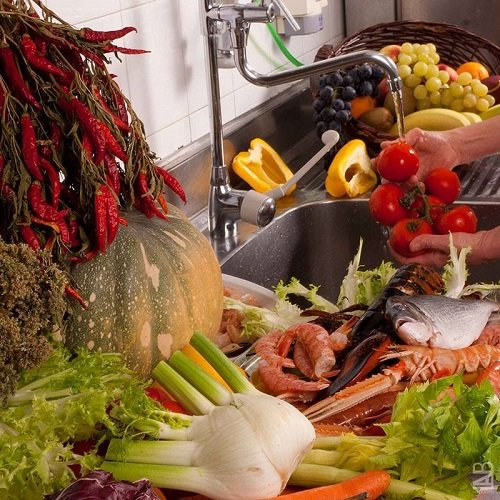 due mani che lavano dei pomodori e accanto della verdura e del pesce