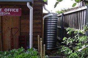 black slimline tank behind house