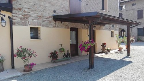 una copertura in legno all esterno con dei vasi di fiori sotto