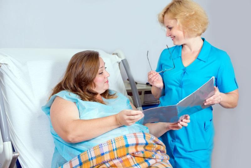 una donna seduta su un lettino ospedaliero e accanto una donna in camice blu