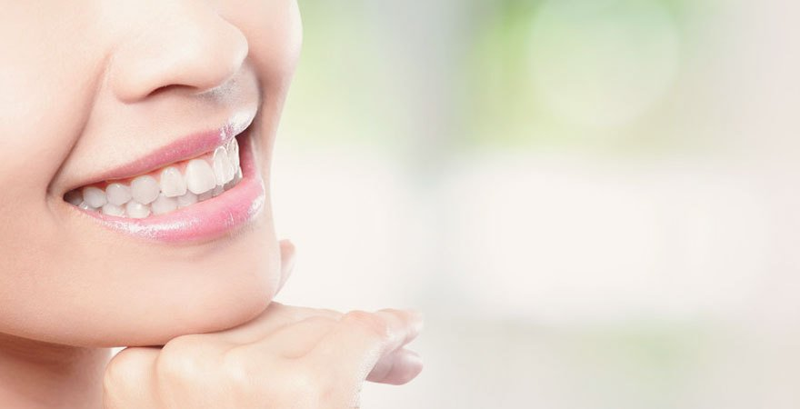A lady with bright white teeth and shiny pink lipstick