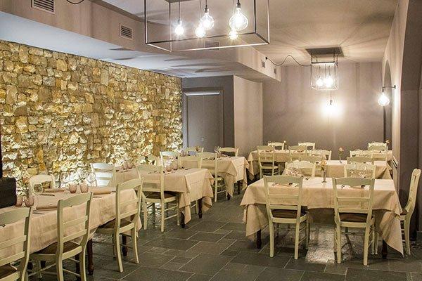 Dei tavoli apparecchiati all'interno di un ristorante e delle luci accese