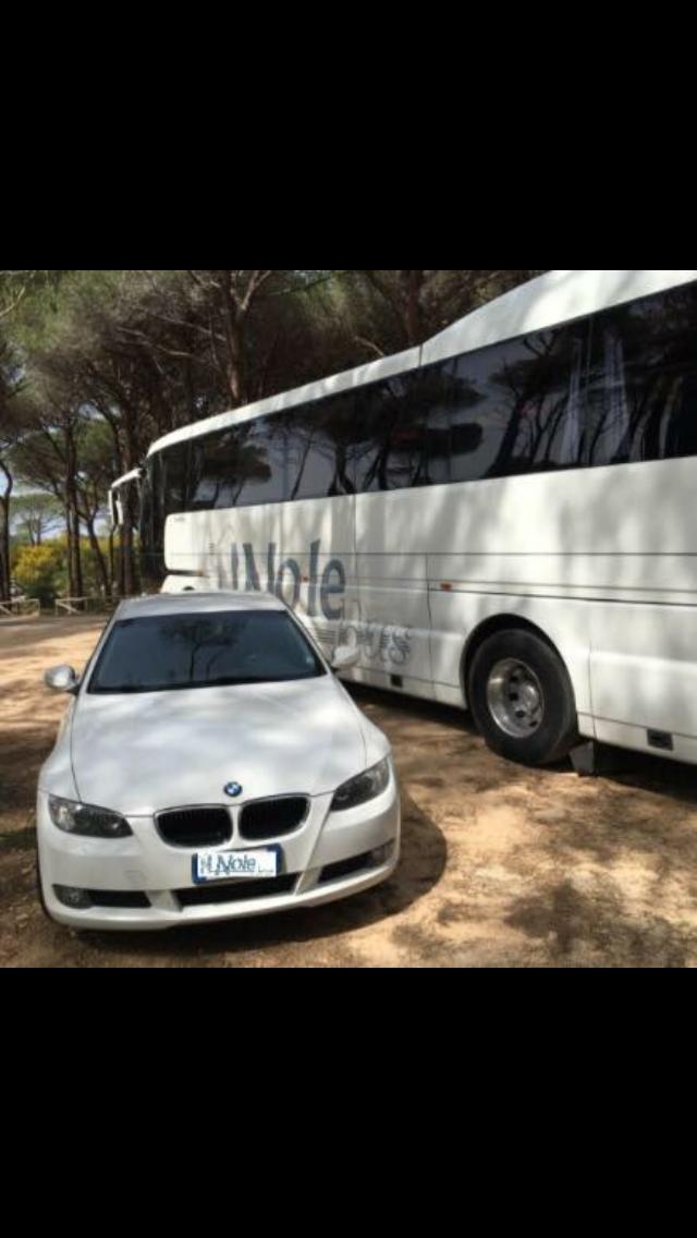 BMW bianca con bus sullo sfondo
