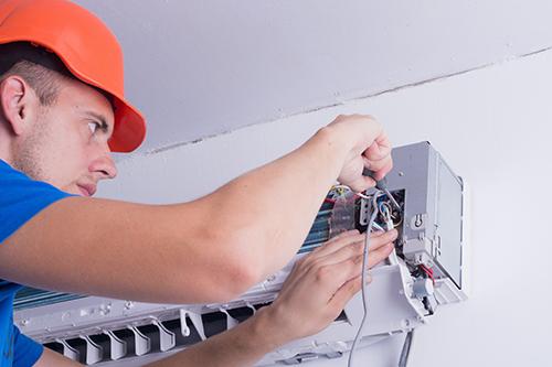 Air conditioner professional repairing the split unit in Wister, OK