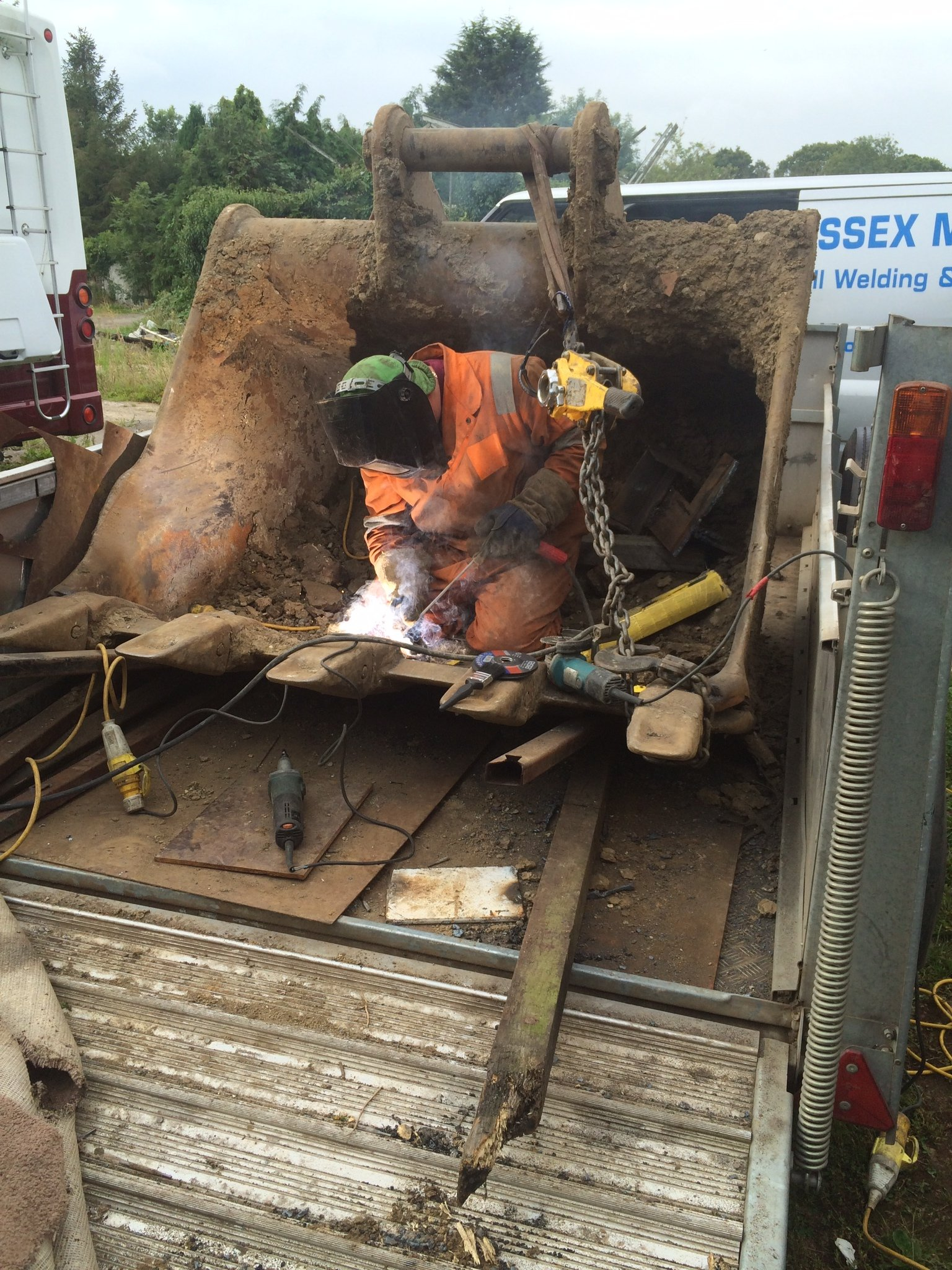 welder in digger bucket