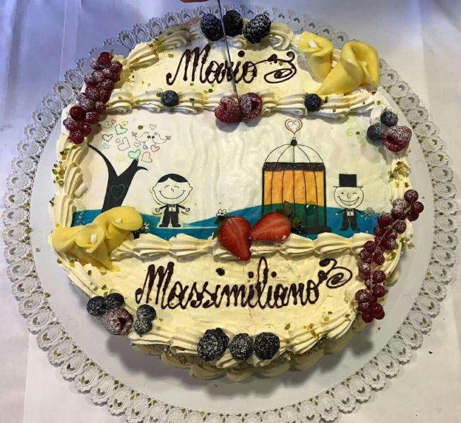 una torta con frutti di bosco e il disegno di due omini con scritto Mario Massimiliano