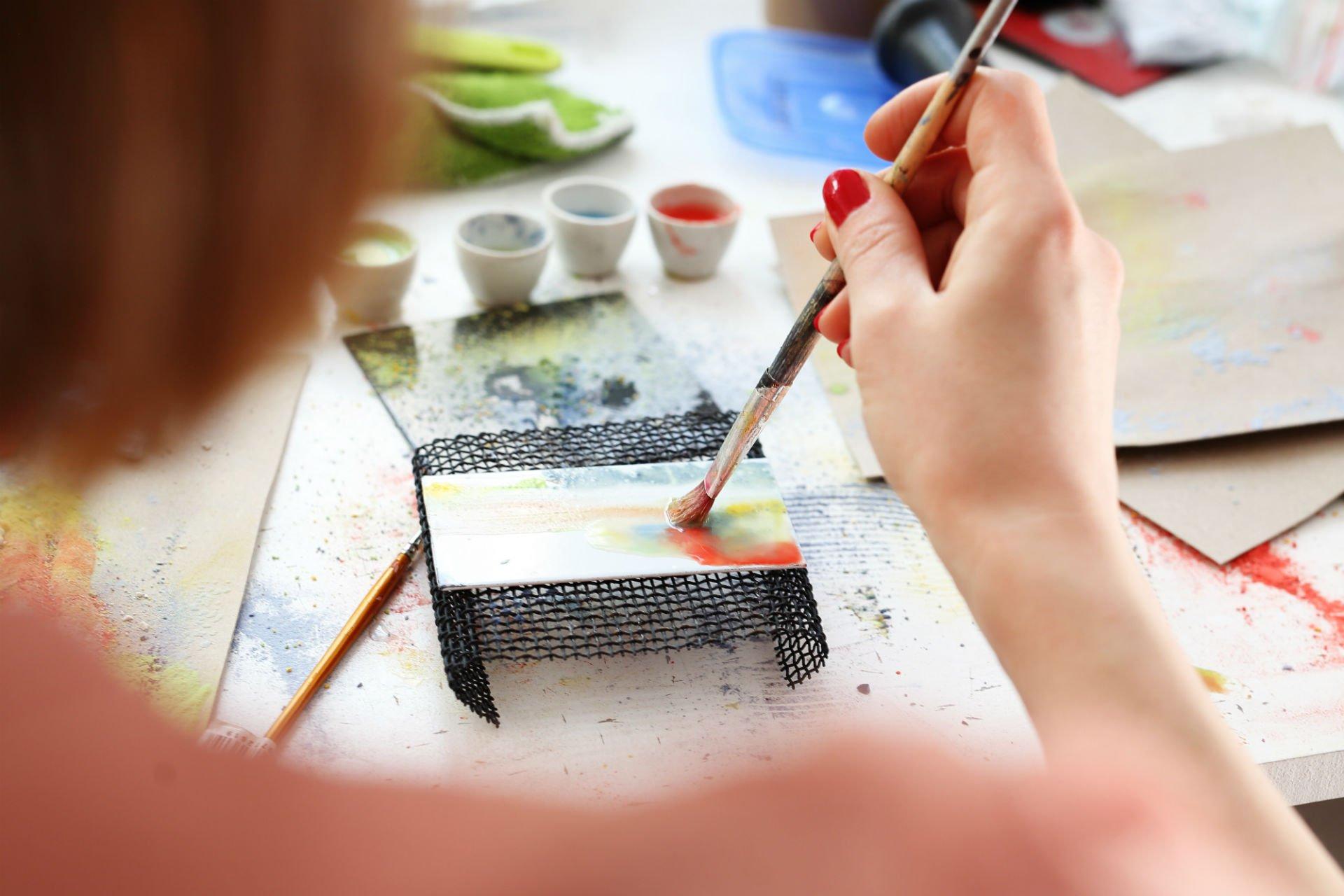 una mano con un pennello che dipinge un oggetto