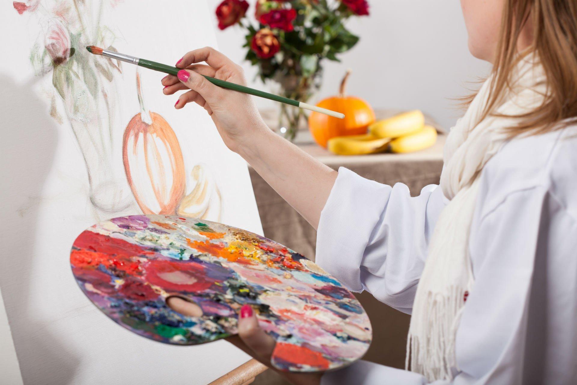 una donna con una tinozza di colori mentre dipinge
