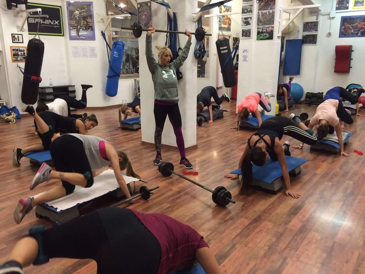 istruttore solleva bilanciere durante lezione di fitness