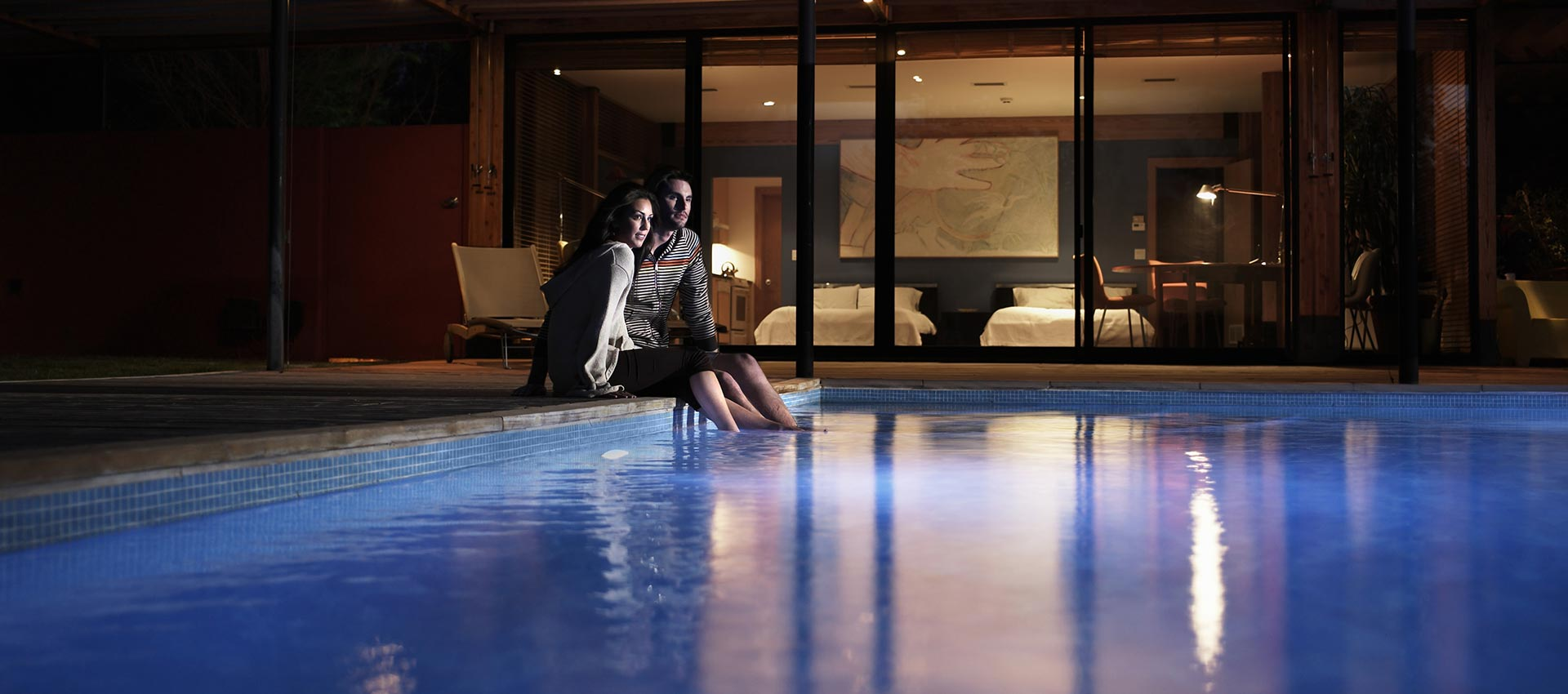 Couple dipping their feet into the pool at night