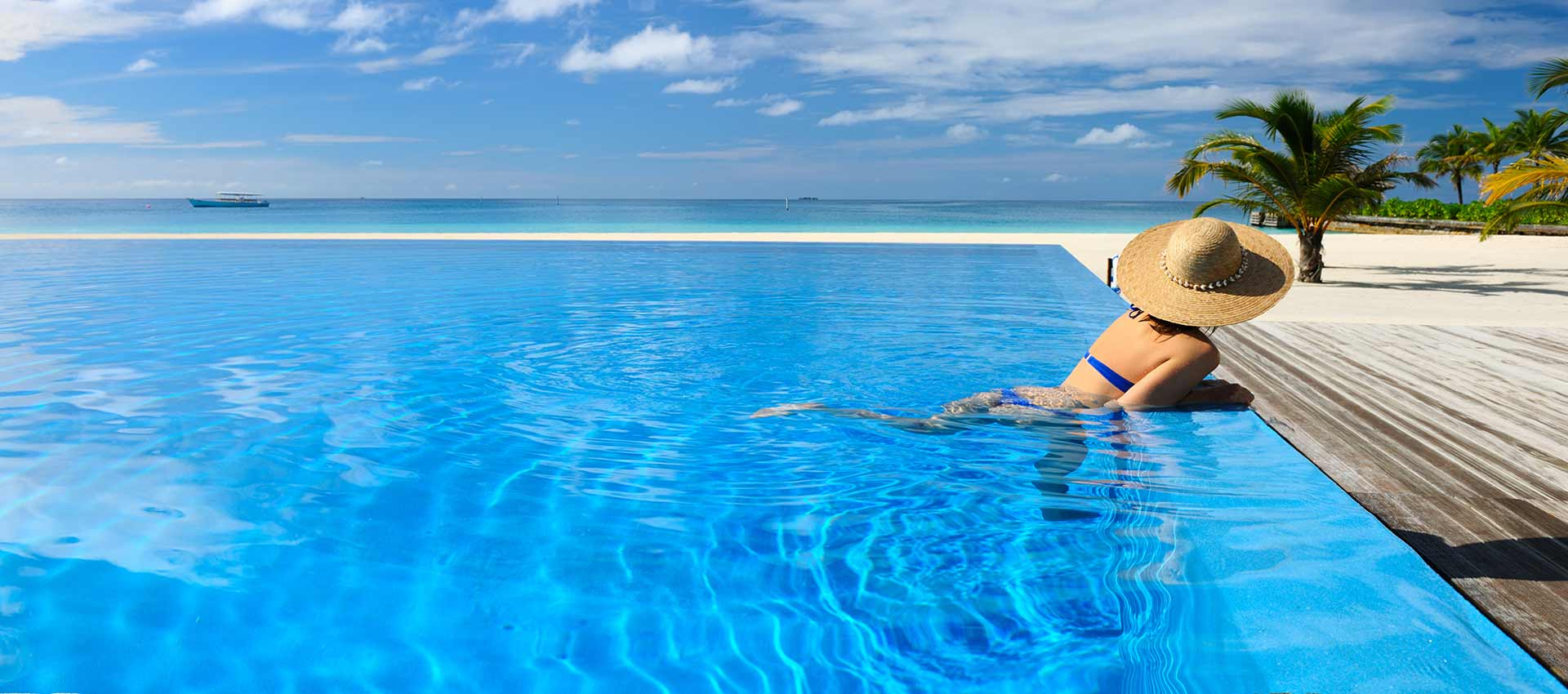 Woman on the edge of an infinity pool overlooking the beach