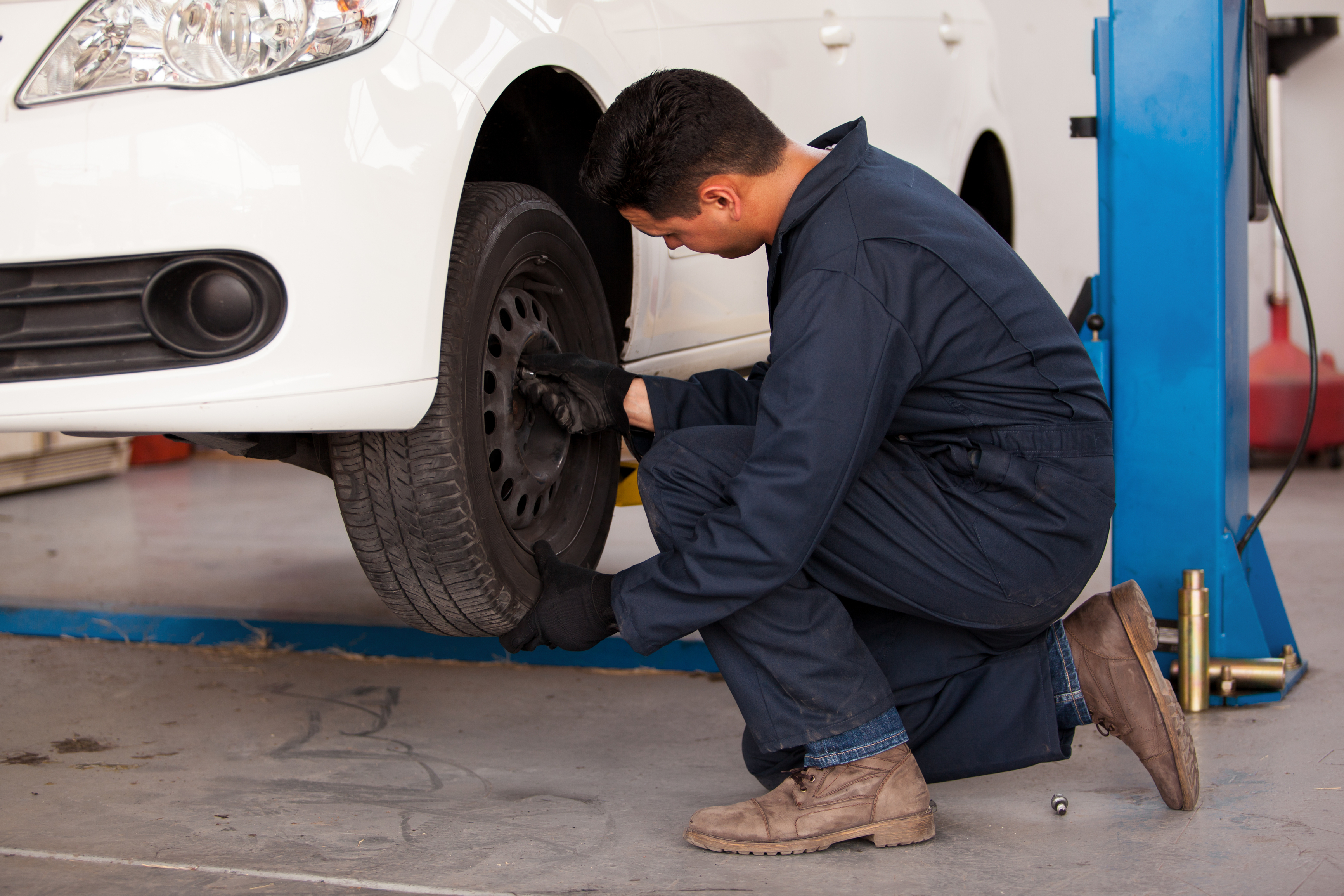 auto mechanic rotating a car's tires
