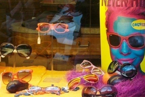 una vetrina con degli occhiali da vista di color arancione, rosa e viola