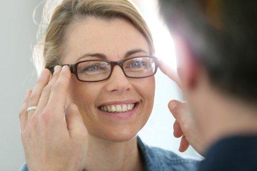 un uomo mentre mette gli occhiali da visita ad una donna sorridente