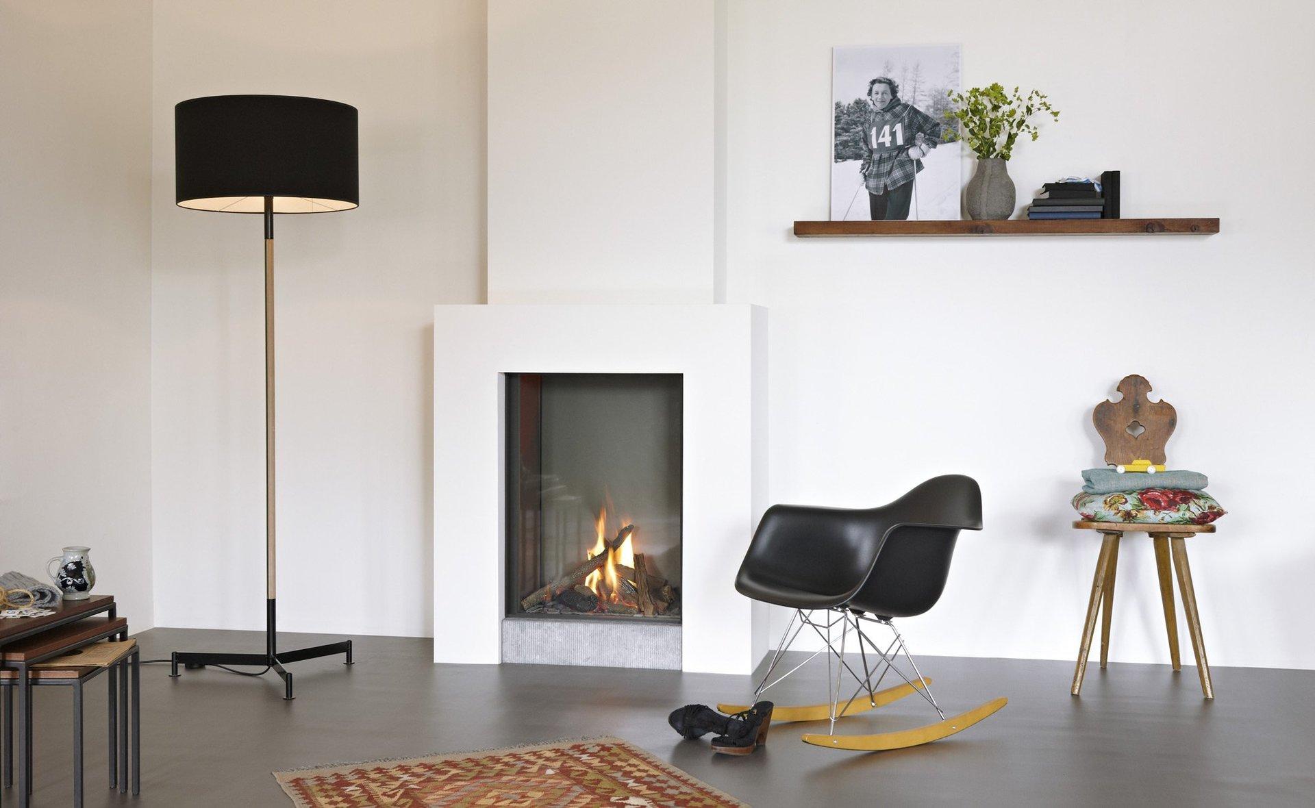 Un camino a legna di color grigio e una sedia  davanti