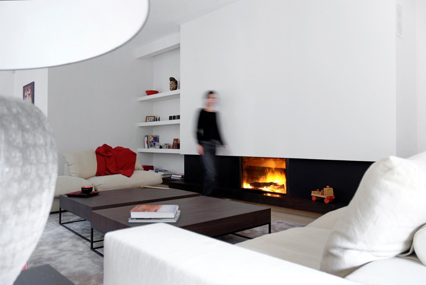 Una sala con divani di color bianco e una stufa moderna