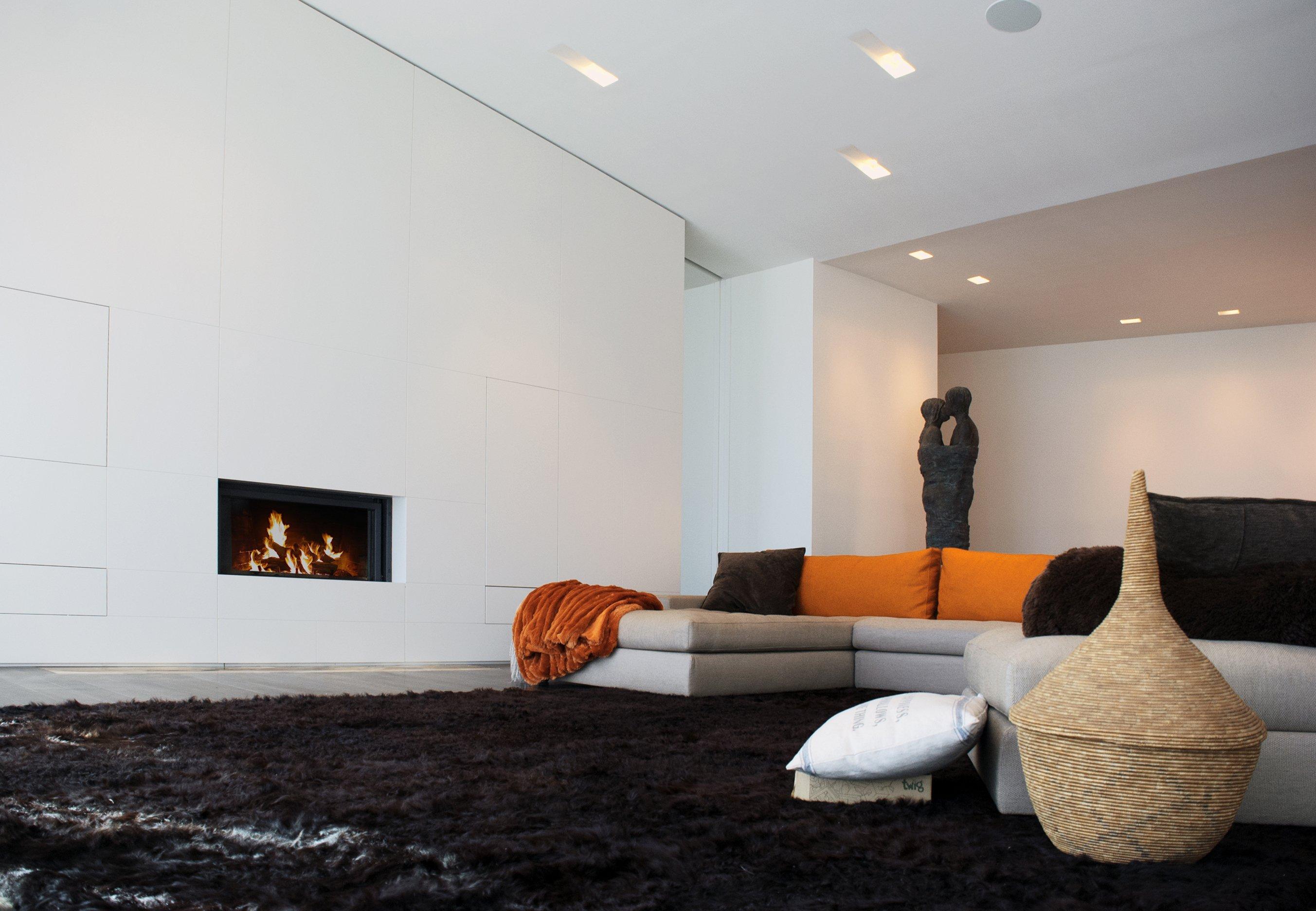 Una sala con un divano angolare e una stufa moderna