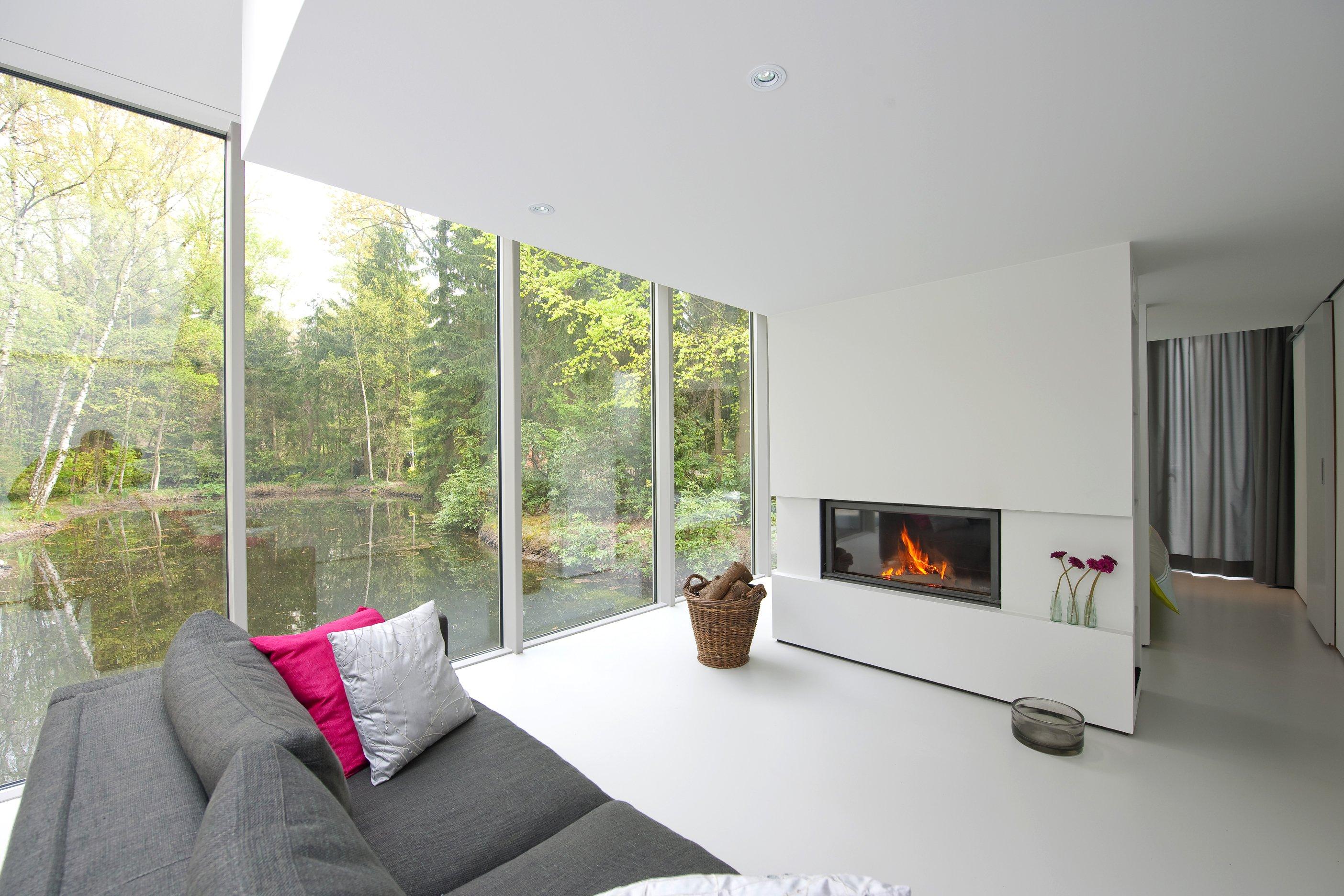 Una sala con un divano di color grigio e una stufa davanti