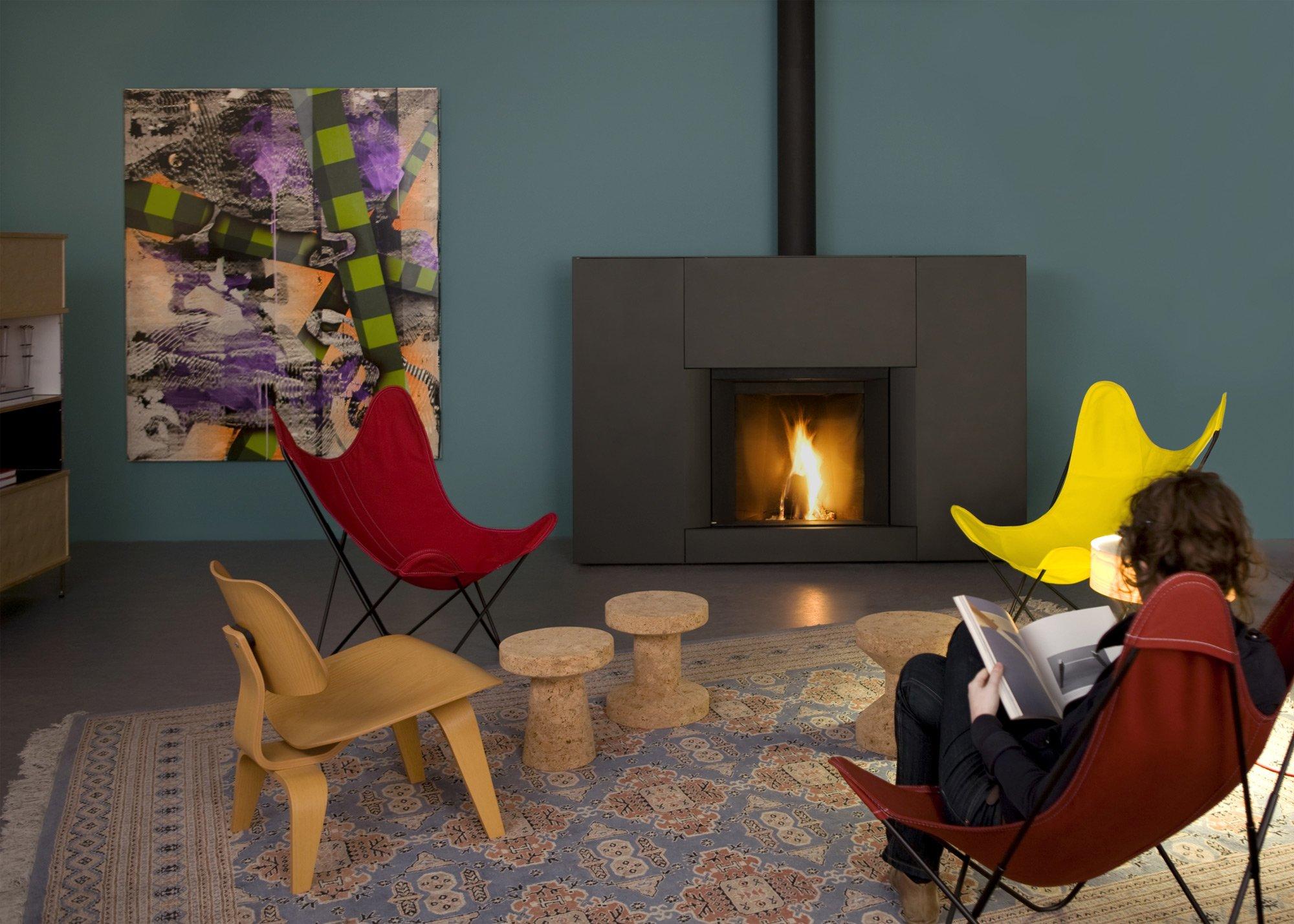 Una sala con un camino e davanti un uomo seduto che legge un libro